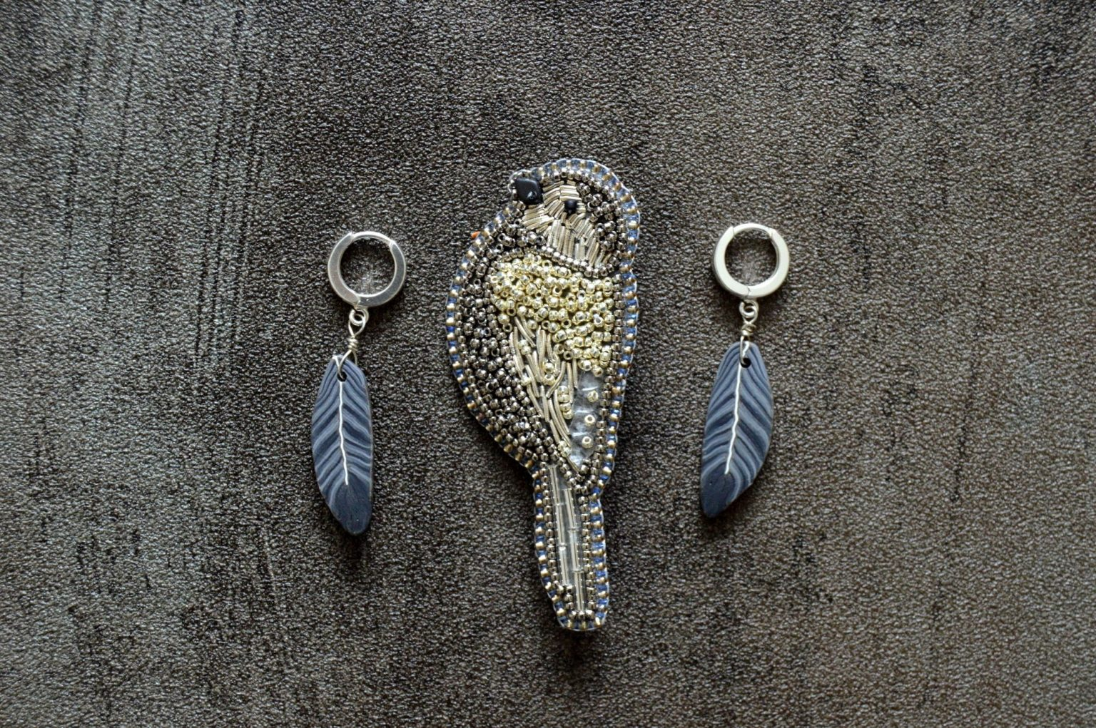 Silver sparrow beaded brooch and black feather earrings